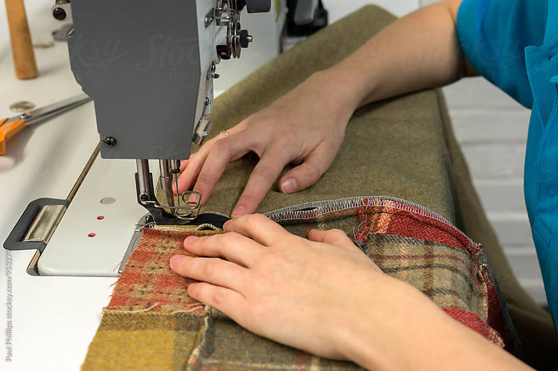 Machine sewing a piece of fabric in a re-upolstery business. by Paul Phillips for Stocksy United