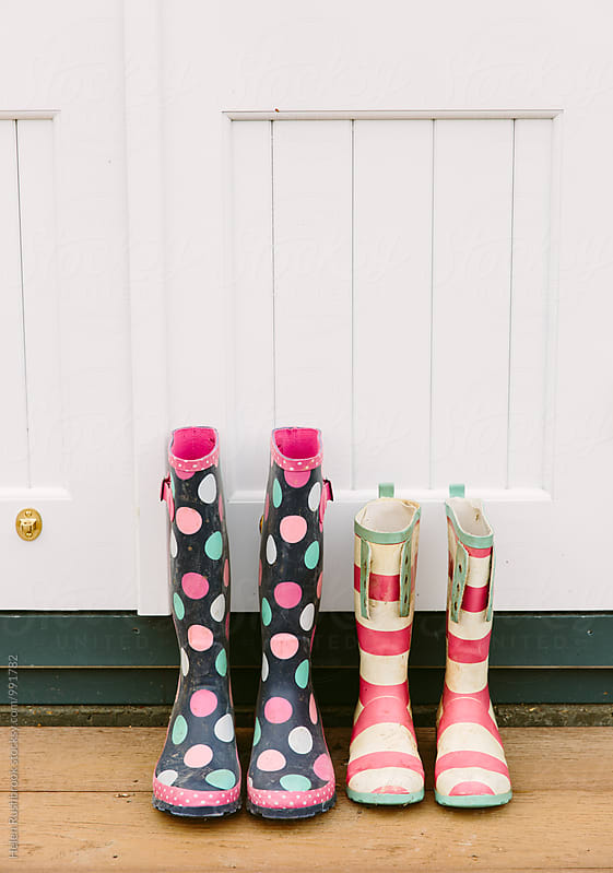 Brightly coloured wellington boots outside a door. by Helen Rushbrook for Stocksy United