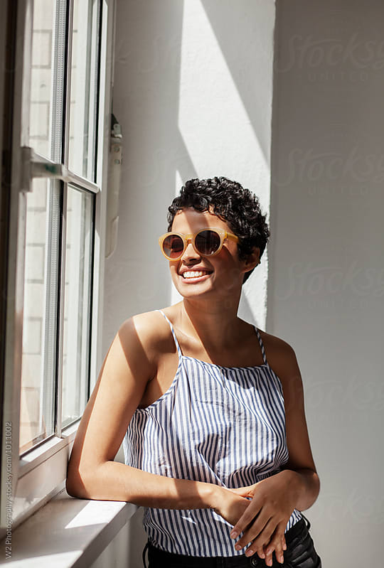 Portrait of smiling young woman wearing sunglasses by a window. by W2 Photography for Stocksy United