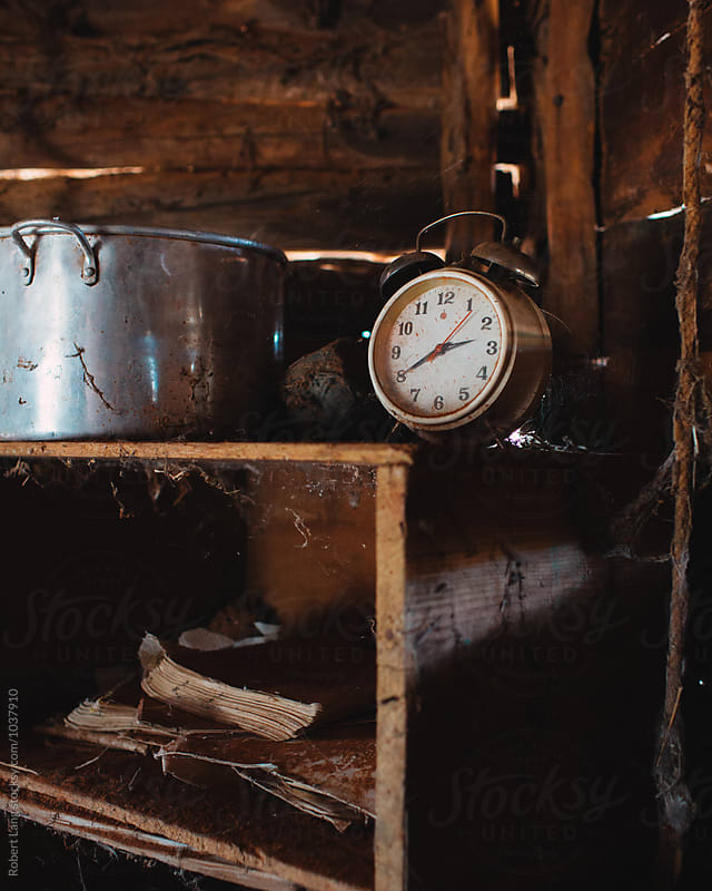 Old alarm clock on a dusty shelf by Robert Lang for Stocksy United