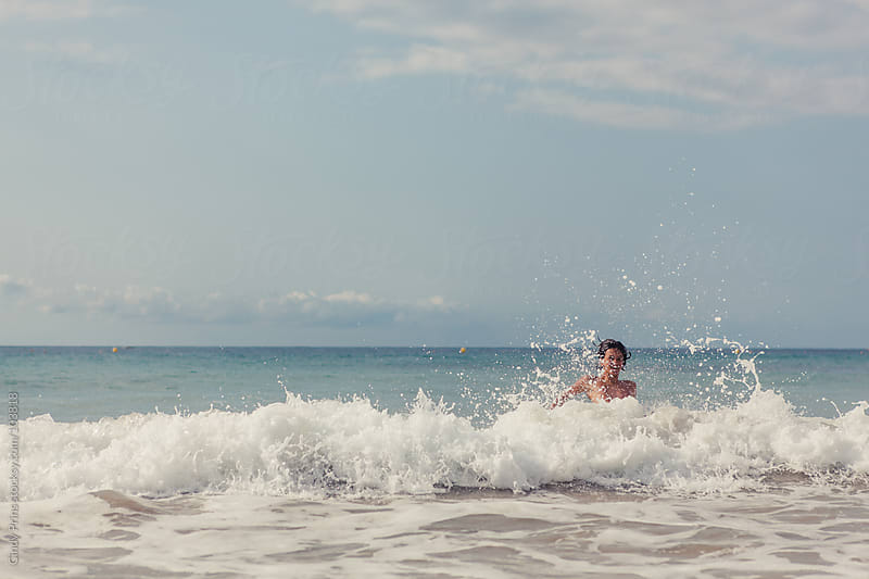 Boy swimming in the ocean playing in the waves by Cindy Prins for Stocksy United