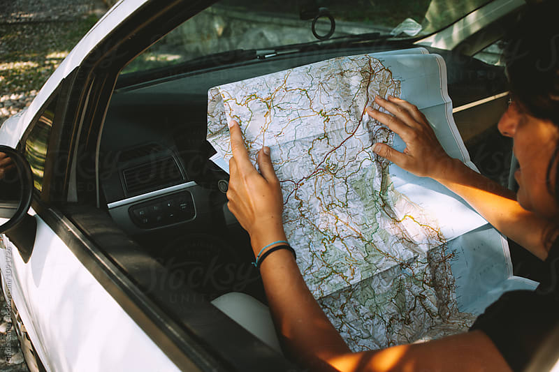 Woman looking at a map in a car by Giada Canu for Stocksy United