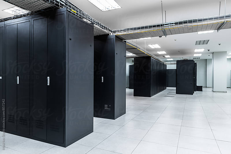 Servers in aisle of storage cabinets in data center by MaaHoo Studio for Stocksy United