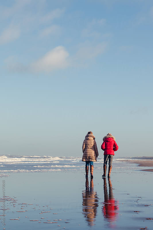 Two older ladies taking a walk on the beach in the winter by Cindy Prins for Stocksy United
