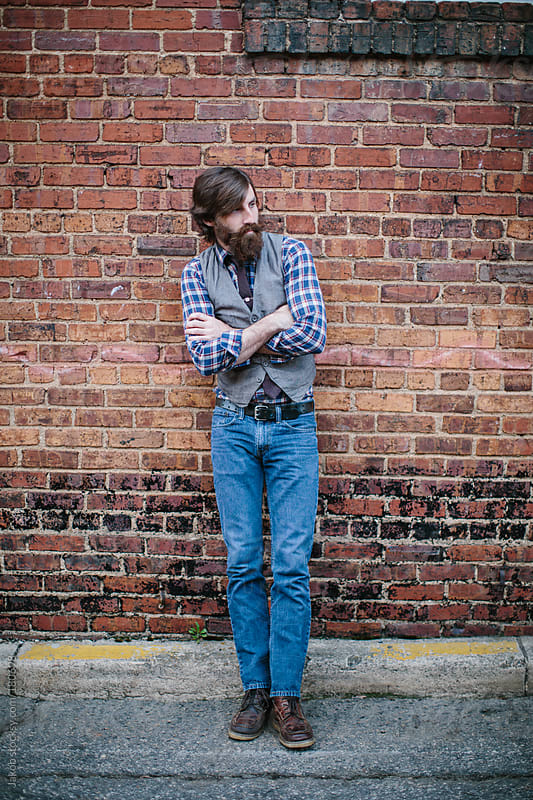 Portrait of a trendy and hip bearded man leaning against a brick wall by Jakob for Stocksy United