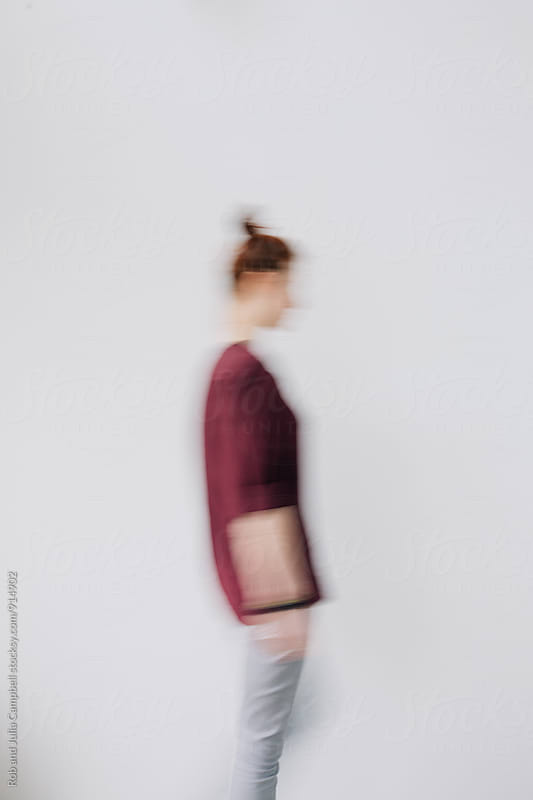Motion blur portrait of red head woman on simple background by Rob and Julia Campbell for Stocksy United