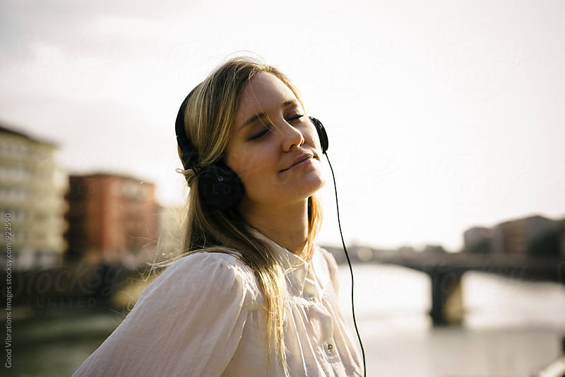 Blond woman listening music outdoors by Good Vibrations Images for Stocksy United
