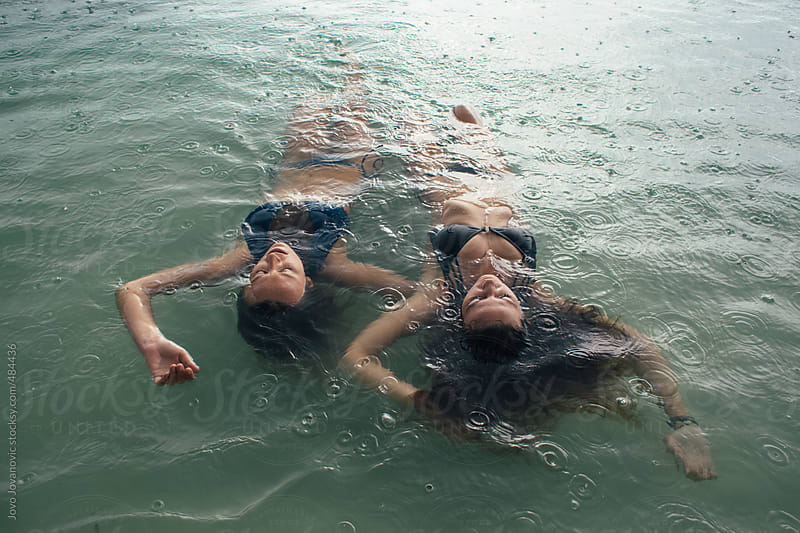 Two girls swimming in the rain by Jovo Jovanovic for Stocksy United