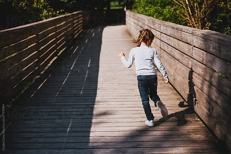 Girl running for fun on a wooden bridge in a park by Giada Canu for Stocksy United