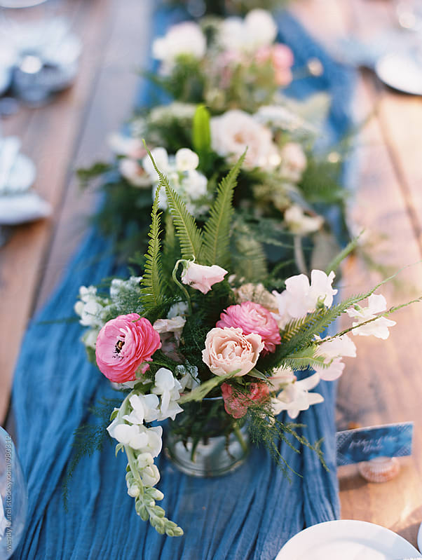 blue runner on table with pink floral centerpiece by wendy laurel for Stocksy United