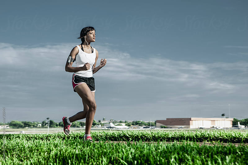 Young Woman Running while Listening to Music by Stephen Morris for Stocksy United