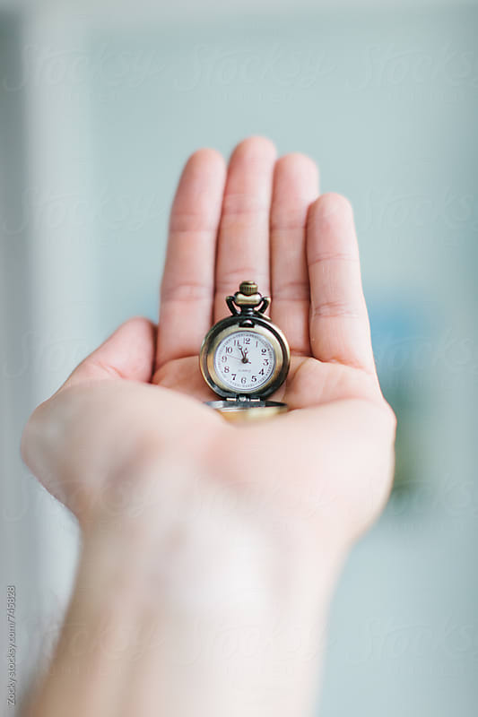 Hand holding mini pocket watch by Zocky for Stocksy United