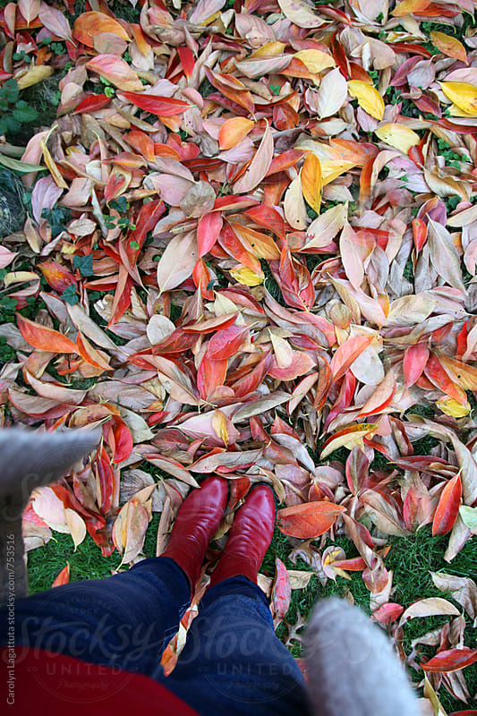 Female in fall clothing and red boots standing in a bunch of fallen leaves by Carolyn Lagattuta for Stocksy United