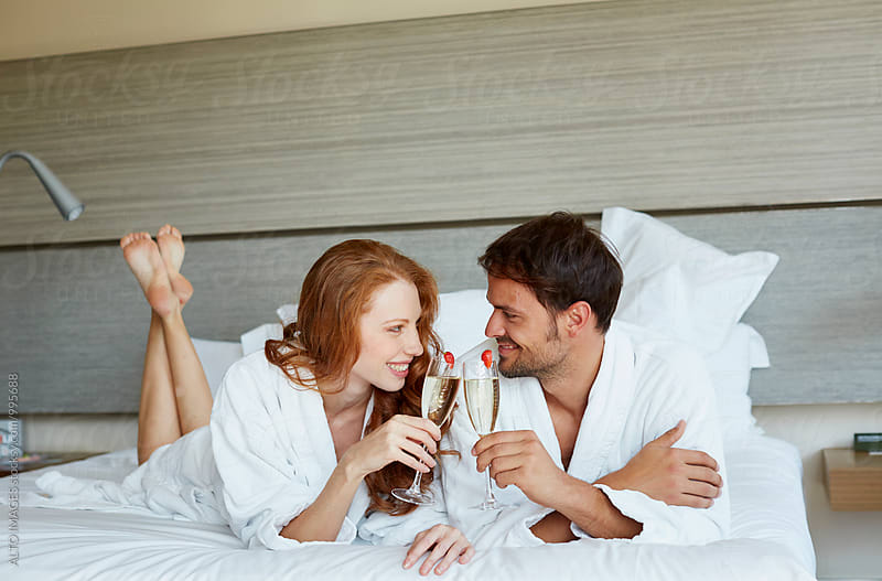 Romantic Couple Toasting Champagne In Bed by ALTO IMAGES for Stocksy United
