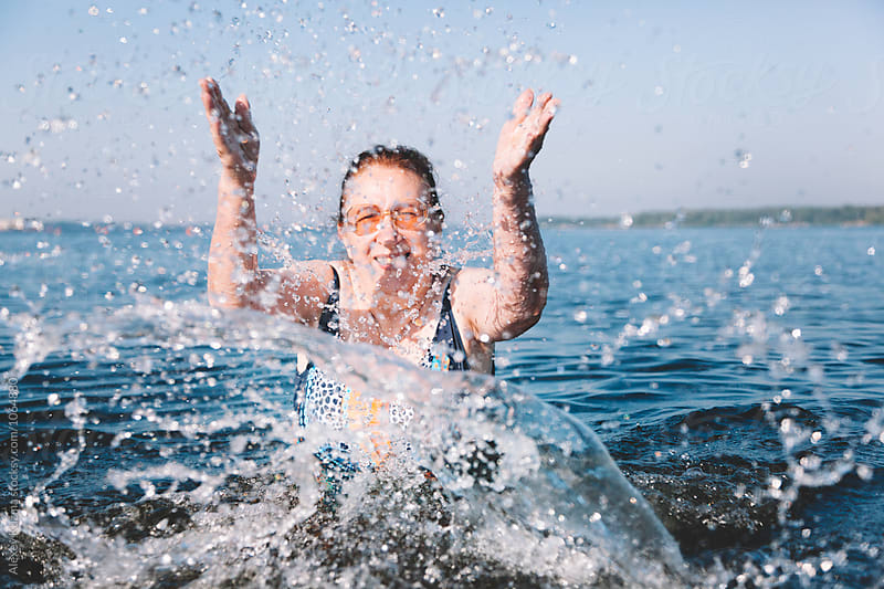 senior woman playing with water by Vesna for Stocksy United