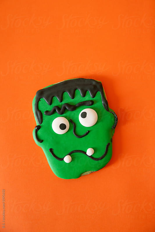Green Zombie frankenstein cookie on a Orange background by B & J for Stocksy United