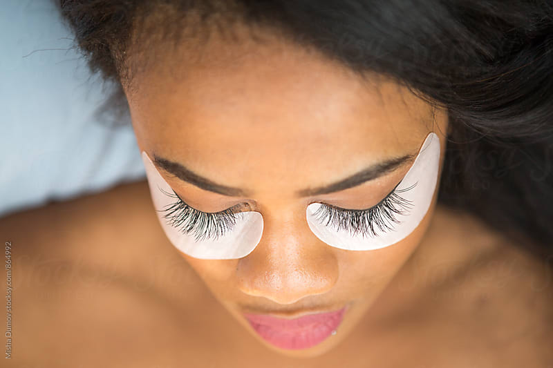Closeup of an African-American woman with eyelash extensions by Mihael Blikshteyn for Stocksy United