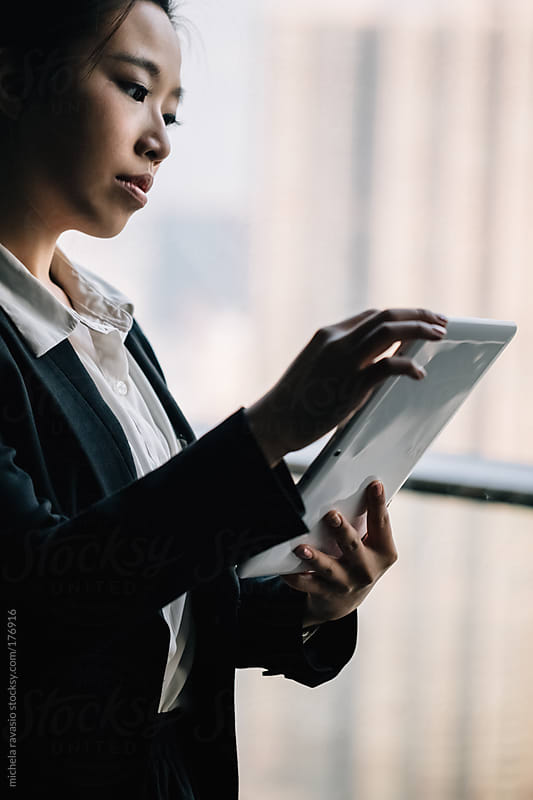 Asian business woman holding a digital tablet by michela ravasio for Stocksy United