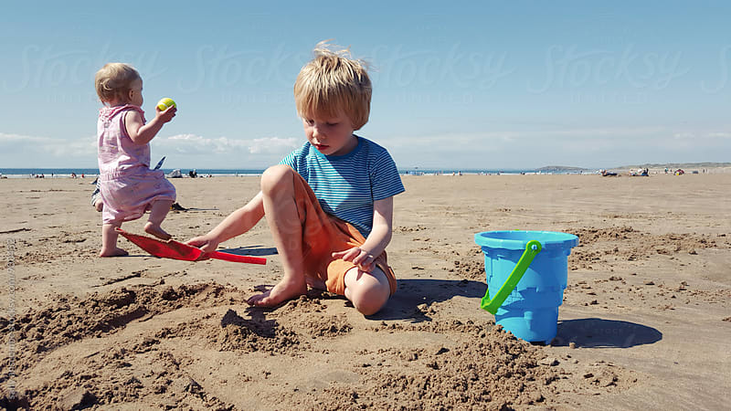 Children playing on the beach by sally anscombe for Stocksy United
