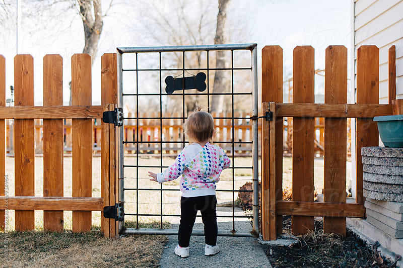 Toddler girl standing at gate by Jessica Byrum for Stocksy United