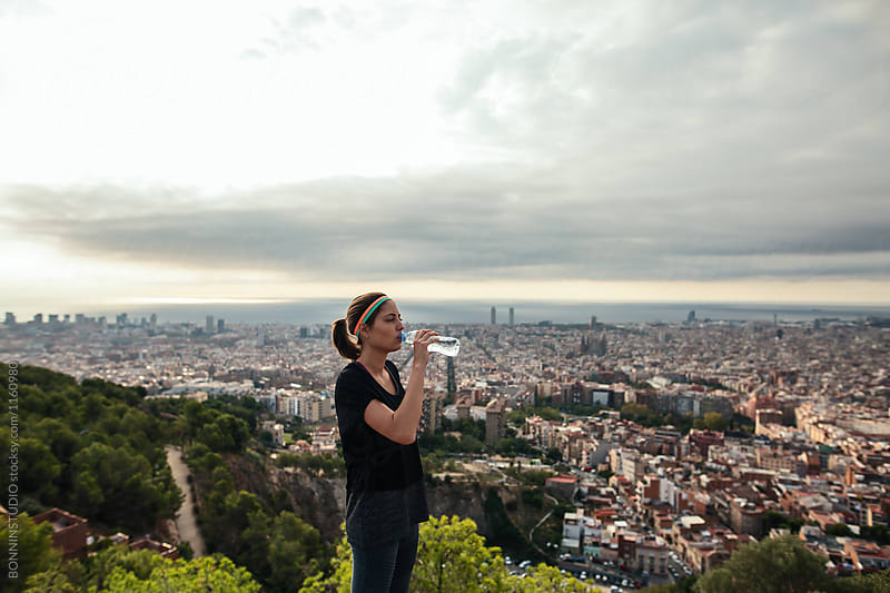 Fit woman resting drinking water after workout above city.