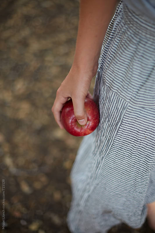 Close up o a young man holding a red apple by Miquel Llonch for Stocksy United