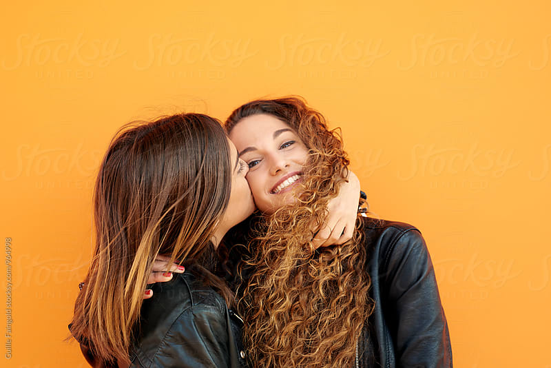 Two best girlfriends against of orange wall by Guille Faingold for Stocksy United