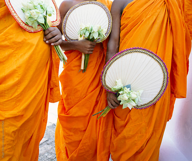 buddhist monks holding lotus flowers by Hugh Sitton for Stocksy United