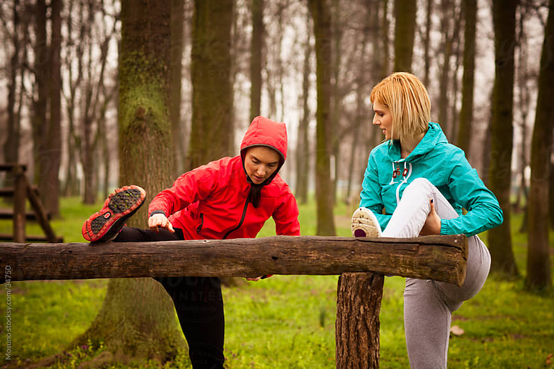 Two young women stretching in the park before jogging. by Mosuno for Stocksy United