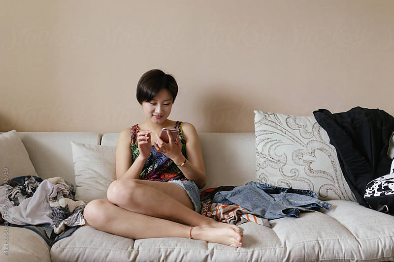Young Asian girl using smartphone at home by MaaHoo Studio for Stocksy United