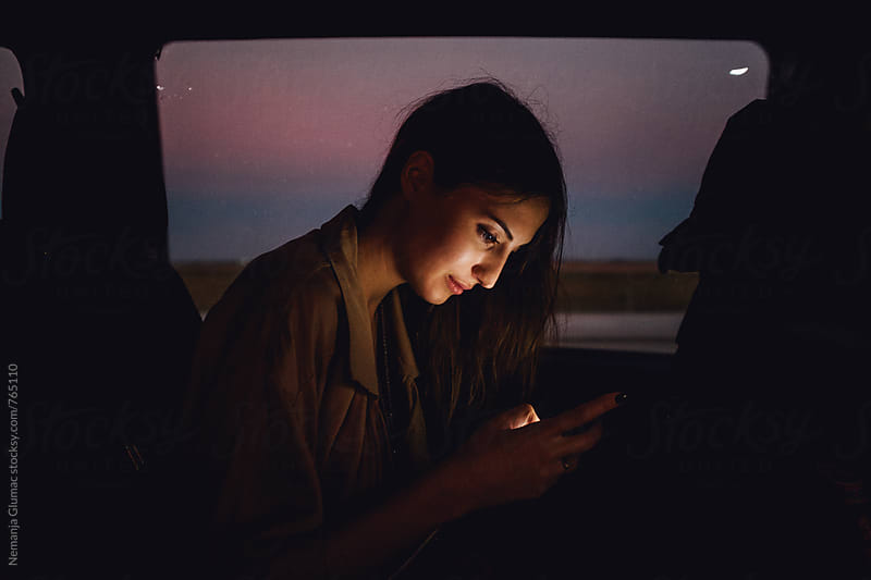 Beautiful Brunette Typing On Her Smartphone in Transport by Nemanja Glumac for Stocksy United