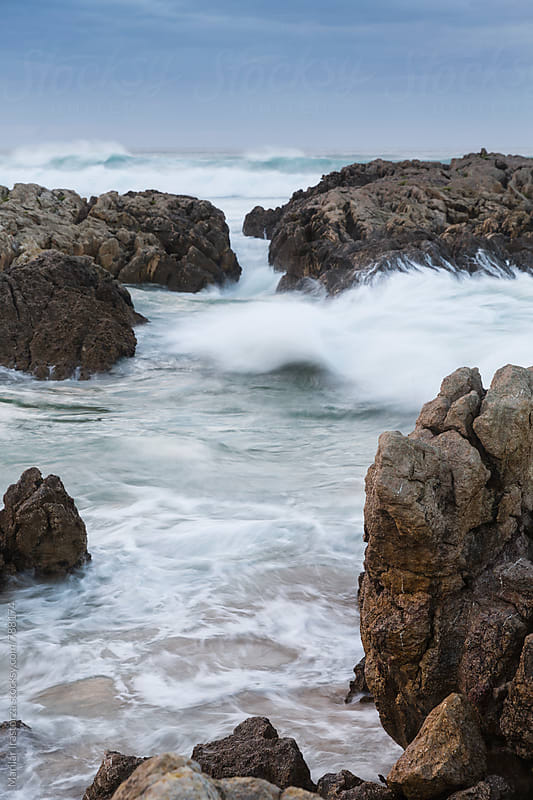 Waves crashing against a rocky shore by Marilar Irastorza for Stocksy United