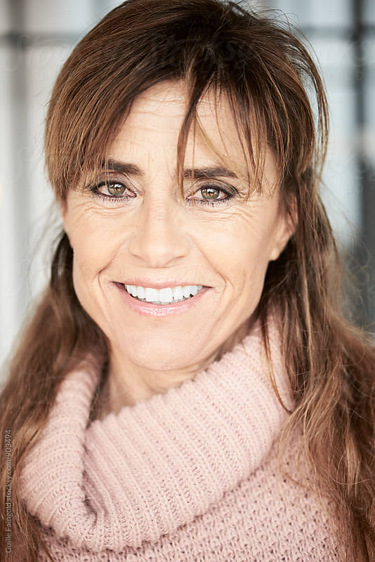 Senior woman with toothy smile looking at camera by Guille Faingold for Stocksy United