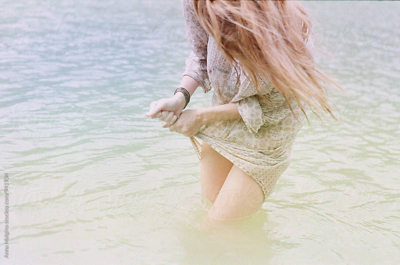 A film photo of young beautiful redhead woman standing in the water by Anna Malgina for Stocksy United