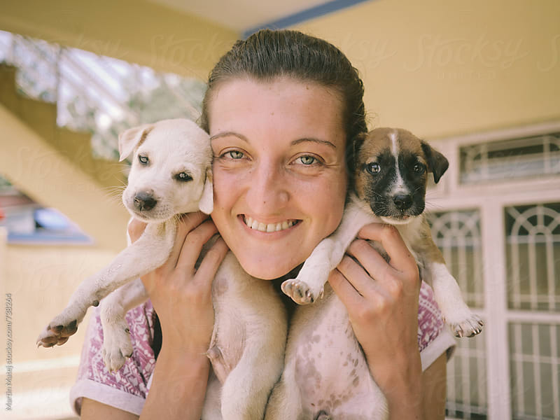 Young girl holding couple of puppies by Martin Matej for Stocksy United
