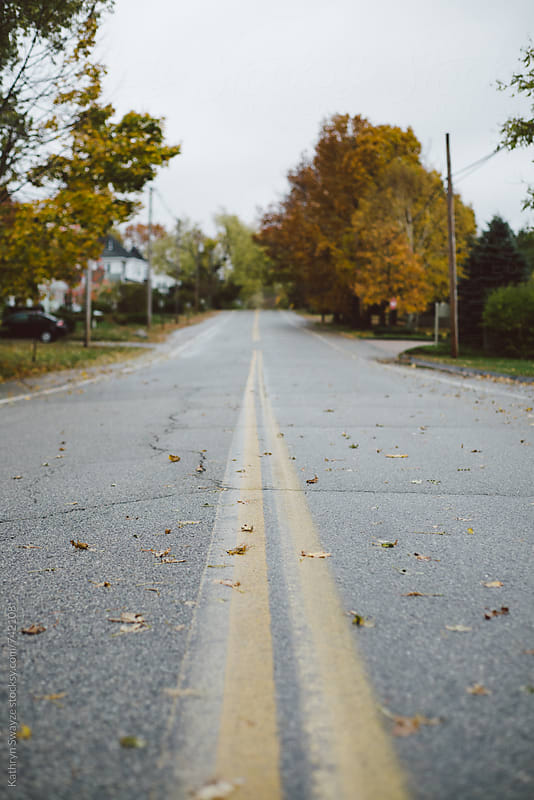 A cloudy gray fall day on a residential road by Kathryn Swayze for Stocksy United