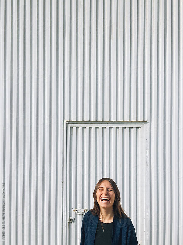 Beautiful young woman laughing outdoors. by BONNINSTUDIO for Stocksy United