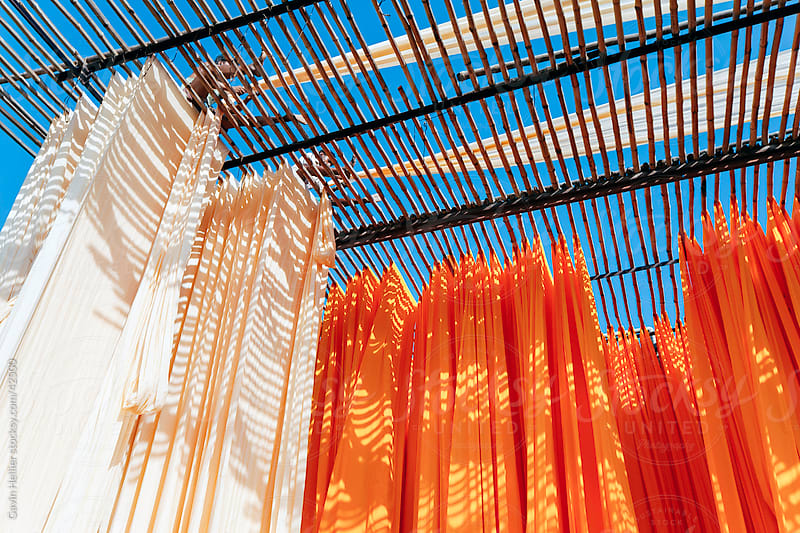 Newly dyed fabric being hung up to dry, Sari garment factory, Jaipur, Rajasthan, India by Gavin Hellier for Stocksy United