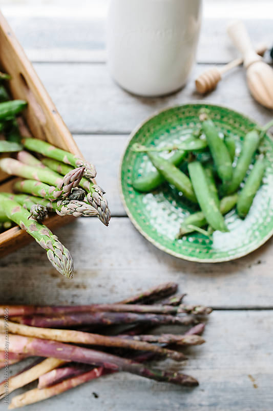Early summer vegetables on a kitchen table. by Helen Rushbrook for Stocksy United