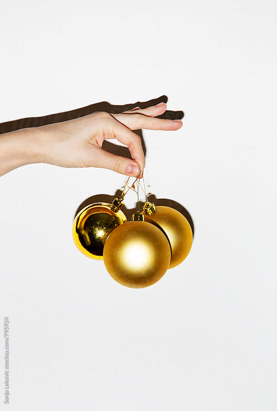 new year's golden decorations in hand on white background by Sonja Lekovic for Stocksy United