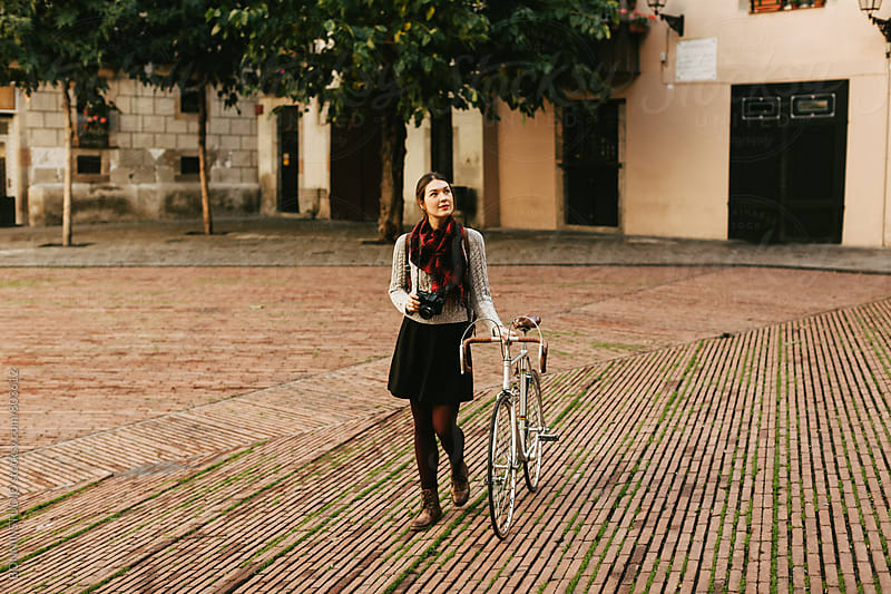 Tourist female walking with her vintage bicycle in the city. by BONNINSTUDIO for Stocksy United