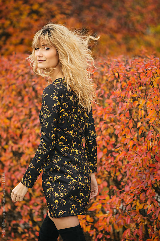 A beautiful blonde woman walking away from the camera smiling on a fall day by Ania Boniecka for Stocksy United