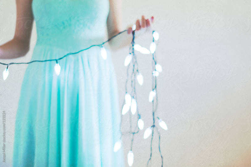 A girl wearing a summer dress holds Christmas lights in her hand by Jacqui Miller for Stocksy United
