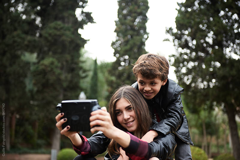 Older sister taking selfie of herself and younger brother by Guille Faingold for Stocksy United