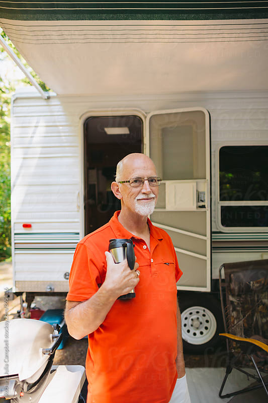 Older gentleman standing outside RV outside by Rob and Julia Campbell for Stocksy United