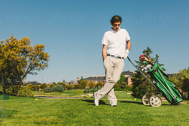 Young Man in a Golf Course  by VICTOR TORRES for Stocksy United