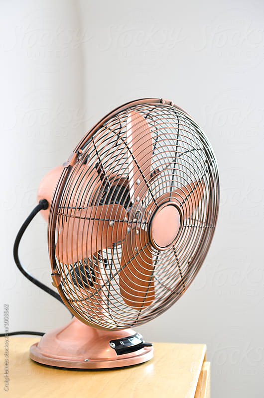Rose gold colored traditional electric fan in a home. by Craig Holmes for Stocksy United