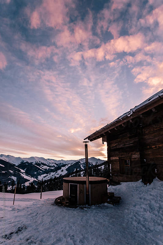 wooden alpine cabin with jacuzzi in alpine winter landscape by Leander Nardin for Stocksy United