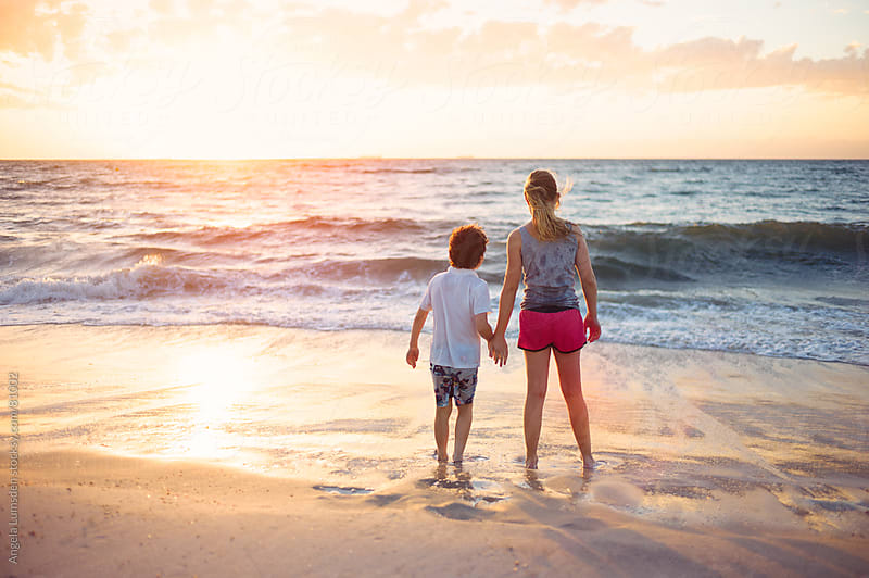 Children standing together at the beach at sunset by Angela Lumsden for Stocksy United