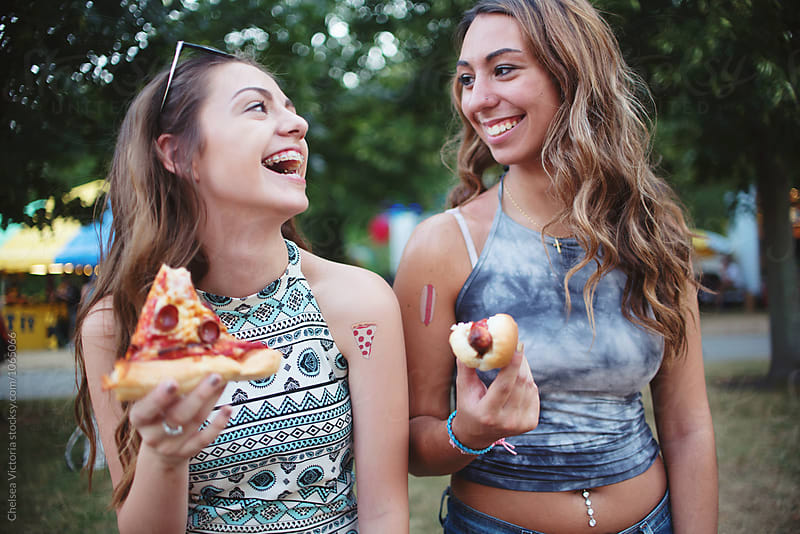 Two young friends eating pizza and hot dogs at a carnival by Chelsea Victoria for Stocksy United